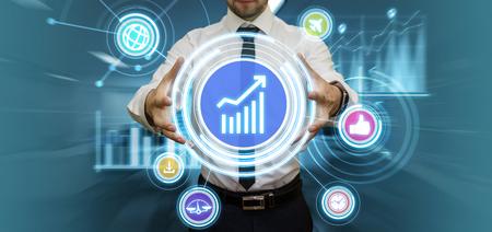 Junger Geschäftsmann, der Darstellung in seinem futuristischen Büro berührt virtuelles Panel mit Medien und finanziellen Graphen. Modernes Business- und Technologiekonzept.