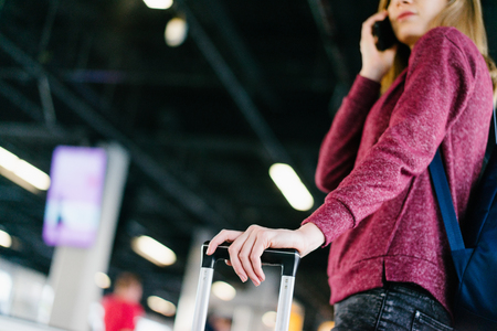Female passenger standing with her bag and backpack and talking on mobile phone while waiting for delayed flight in the international airport terminal. Cropped shot with blurred background. Stock Photo