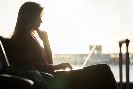Freelancer girl working distantly using her laptop while waiting for her flight in the international airport terminal. Silhouette in front of the window. Modern job and distant education concept.