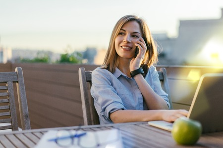 Young attractive casual dressed freelancer woman sitting on sunlight filled terrace working on her project using laptop and answering phone call. Distant job in comfortable conditions concept. Side view.