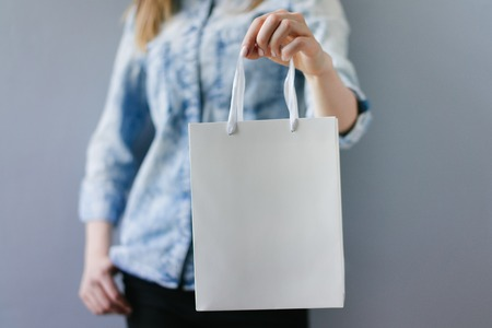 Cropped shot of female hands holding blank white paper bag in her hand. Front view, horizontal. Mock up, copy space for your text or logo.