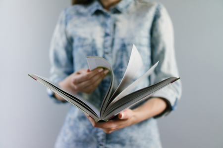 Close up cropped shot of  female hands holding open book, leafing it through, looking for page needed. Studying, education, new knowlege concept. Plain grey background. Horizontal placement. Front view. Archivio Fotografico