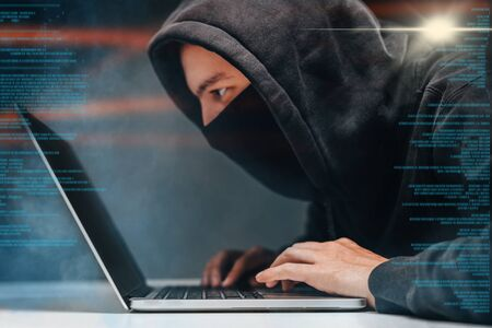 Male hooded hacker with hidden face accessing to personal information on laptop in the dark. Technologal, cyber crime concept. 免版税图像