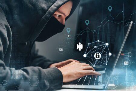 Hombre vestido con sudadera con capucha y máscara pirateando información personal en una computadora en una oficina oscura con fondo digital. Concepto de delito cibernético, deep web y ransomware.