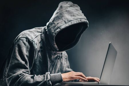 Internet crime concept. Male hooded hacker with obscured face accessing to personal information on laptop a dark room. 免版税图像