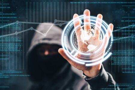 Male hacker accessing to personal information. Hooded man with obscured face touching digital panel with mixed media and binary code. Technologal, virtual crime, cybersecurity concept.