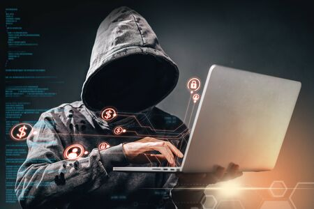 Male hooded hacker with hidden face accessing to personal information on laptop in the dark. Digital background with binary code and mixed infographics. Deep web, ransomware, cyber crime concept.
