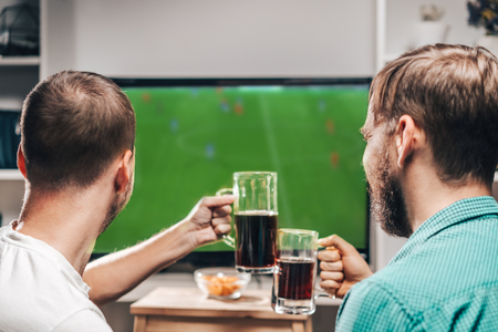 Two male buddies watching live football game broadcast on tv, cheering and drinking beer. Friends spending their day-off together at home.