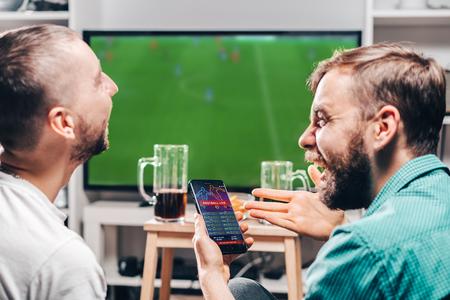 Due amici maschi che guardano la partita di calcio in diretta trasmessa in tv e celebrano la vittoria in denaro dopo aver effettuato scommesse online sul sito Web dei bookmaker.