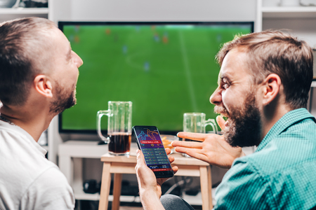 Two male buddies watching live football game broadcast on tv and celebrating money win after making bets online at bookmakers website. Stockfoto