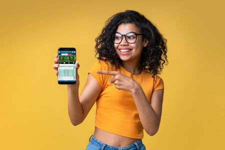 Cute african american girl watching football play online broadcast cheering for her favourite team and being happy about the score pointing at her mobile phone screen. Her bet played. Isolated shot.