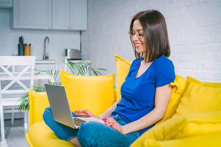 Attractive casually dressed girl with charming smile working from home using her laptop computer. Freelance, distant work and education, self isolation concept.