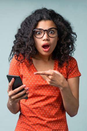 Shocked hipster girl in trendy spectacles pointing at her mobile phone with index finger looking amazed with mouth open and pop-eyed face expression unable to believe she won a bet. Grey backdrop Imagens