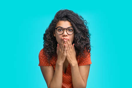 Beautiful young astonished woman in trendy eyeglasses sitting isolated on bright colored blue background looking shocked covering her mouth with hands reading last news.