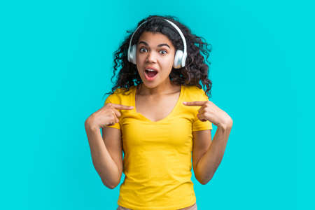 Cute surprised girl in wireless earphones pointing at herself with index fingers with amazed face expression.