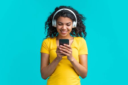 Beautiful smiling dak skinned girl chilling listening to music with wireless earphones and browsing playlist on mobile application on her smartphone.