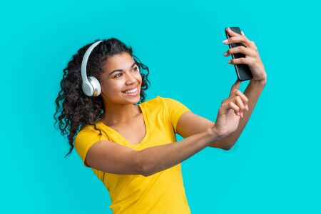 Charming young woman in wireless headphones listening to music and taking selfie on her mobile phone. Cute girl with perfect smile having video conference with her boyfriend. Imagens