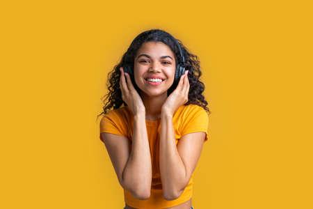 Beautiful dark skinned girl enjoying listening to music with wireless headphones.