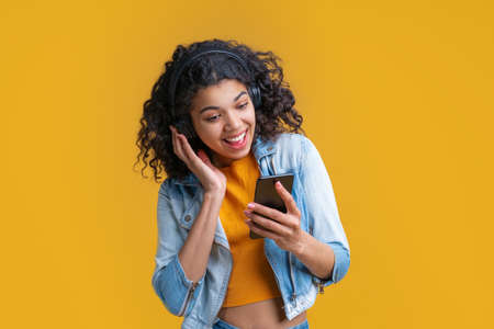 Cute smiling dark skinned girl in wireless headphones enjoying listening to music using application on her mobile phone.