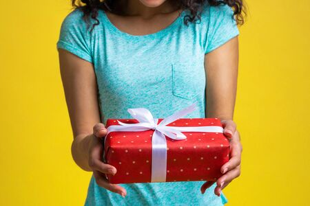 Cropped shot of woman hands holding gift box decorated with satin ribbon.