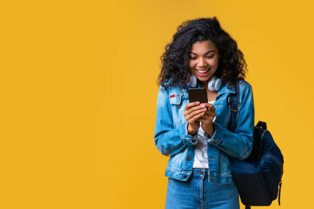 Happy smiling casually dressed passenger with a backpack and bag browsing her mobile phone while waiting for her flight. Studio shot isolated over yellow background.