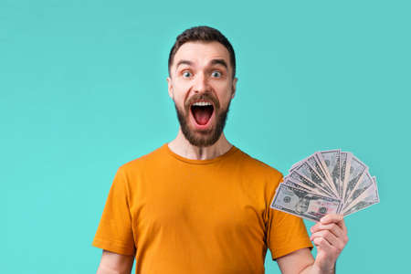 Euphoric football fan celebrating his favourite team victory and money win at bookmaker's website showing sincere excitement screaming and laughing. Imagens