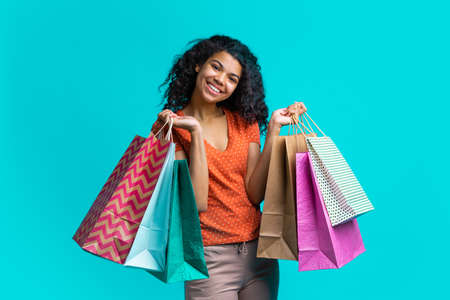 Cute dark skinned girl with perfect smile posing with piles of shopping bags isolated over bright blue background. Shopping, sales, black friday concept. Imagens