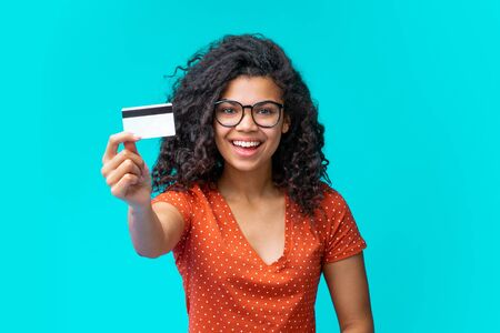 Studio portrait of happy attractive young african american woman in trendy spectacles smiling and holding credit card in hand. Isolated over blue background. Imagens