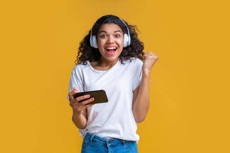 Studio shot of cute happy dark skinned girl wearing earphones, holding smartphone and looking at the camera smiling making winner gesture yes celebrating success.