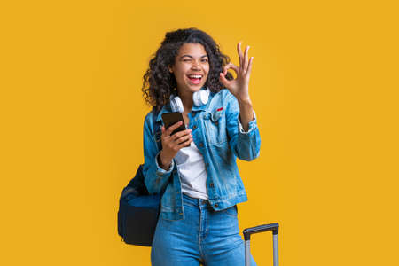Happy cute casually dressed tourist girl with backpack and mobile phone winking and showing ok gesture. Isolated over yellow background.