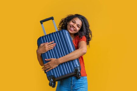 Smiling cute dark skinned girl hugging her hand luggage bag happy to travel. Isolated over yellow background.
