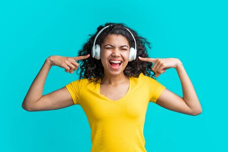 Beautiful young woman in headphones listening to music , smiling and singing isolated over blue background.