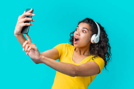 Cute african girl in wireless headset taking selfie with amazed mouth open face expression on her mobile phone. Imagens