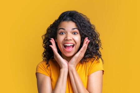 Portrait of young attractive african american woman looking shocked with eyes and mouth wide open. Isolated on bright yellow background. Imagens