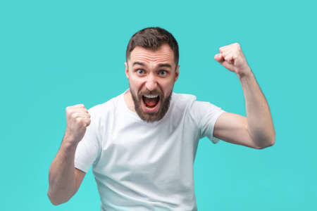 Young bearded male hipster feeling euphoric about money win after making bets at bookmaker's website. Lucky football fan celebrating his favourite team victory clenching his fists up.
