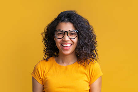 Portrait of young attractive african woman in trendy spectacles on bright background. Cute girl with voluminous curly hair looking happy with wide perfect smile on her face.