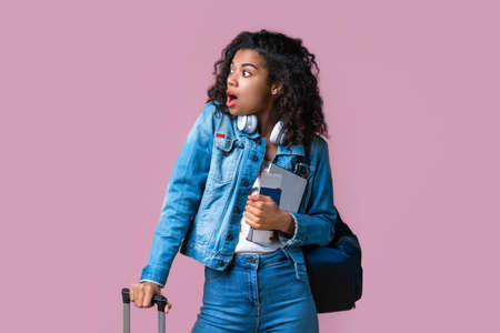 Shocked female passenger with mouth open listening to her flight cancellation announcement isolated on pink background. Imagens
