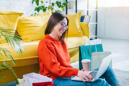 Beautiful female fashion blogger making online purchases from home sitting in cozy living room with her laptop computer and coffee cup