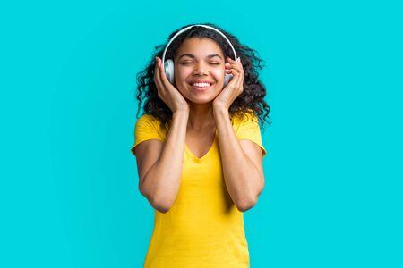 Smiling beautiful young woman in headphones enjoying listening to music