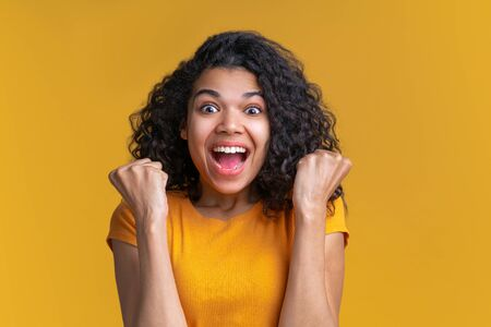 Studio shot of cute african american girl on bright yellow background