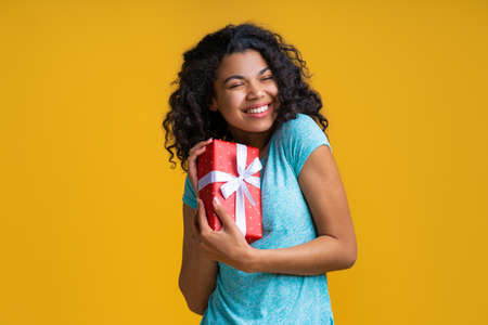 Portrait of young casually dressed dark skinned woman holding gift box decorated with satin ribbon in hands showing sincere happiness