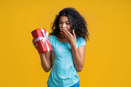 Portrait of astonished young african girl holding unexpected gift box decorated with satin ribbon covering her mouth with a hand in surprise Imagens