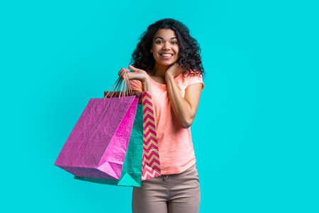 Emotional dark skinned girl with a bunch of shopping bags showing sincere excitement getting her purchases at a very favorable price