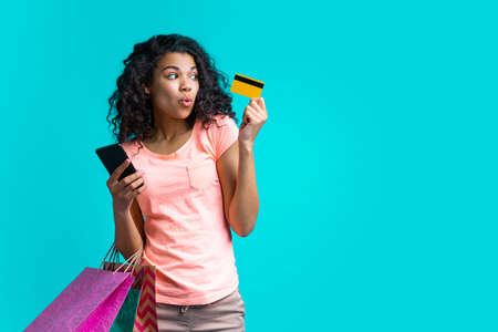 Beautiful female fashion blogger with a bunch of shopping bags holding credit card and mobile phone in hands. Online shopping concept.