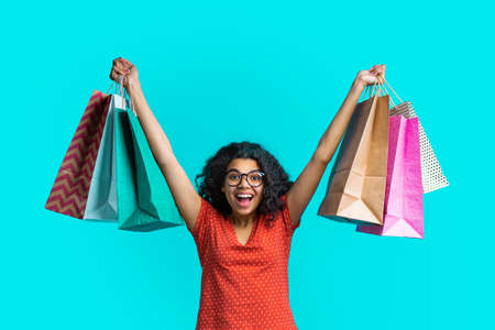 Emotional dark skinned girl with bunches of shopping bags showing sincere excitement getting her purchases at a very favorable price