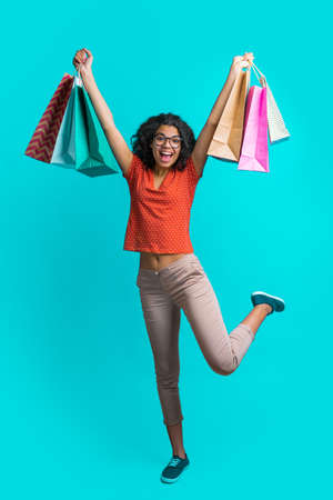 Vertical shot of excited dark skinned girl with a bunch of shopping bags jumping over bright blue background with broad smile on her face