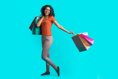 Full- length portrait of cute dark skinned girl with perfect smile standing with pile of shopping bags isolated over bright blue background Standard-Bild