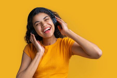 Studio portrait of cute smiling casually dressed dark skinned girl in wireless headphones enjoying listening to music and singing isolated over bright colored yellow background Imagens