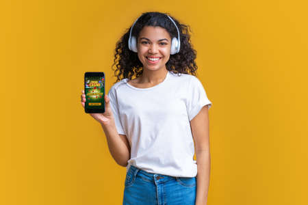 Smiling cute dark skinned girl in wireless earphones showing her phone screen to the camera with bookmakers website interface Imagens