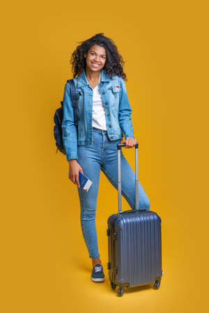 Full- length portrait of cute dark skinned tourist girl posing with hand luggage bag and backpack
